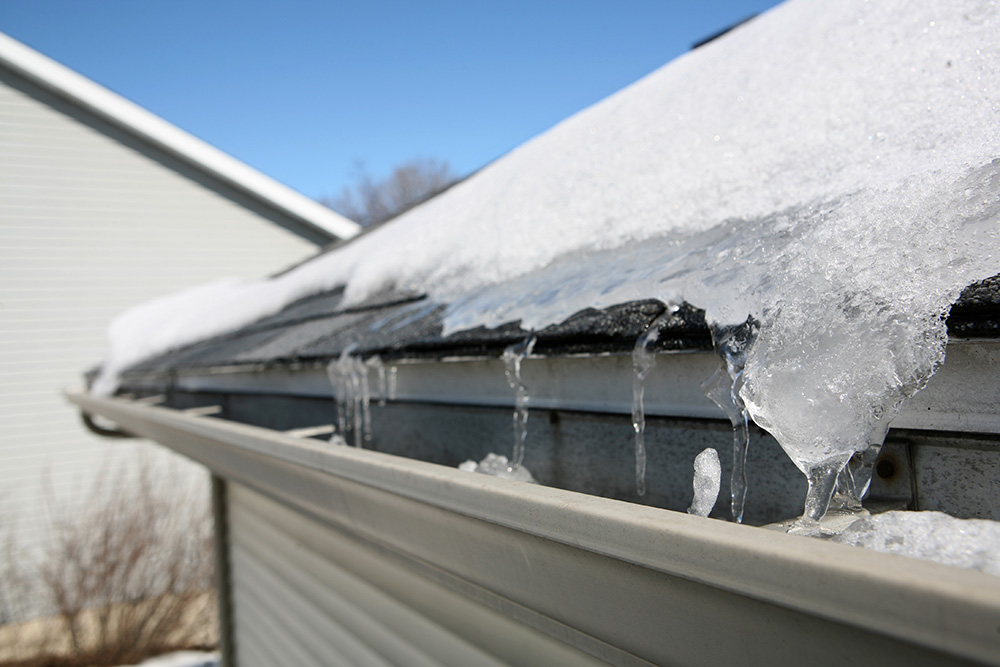 A roof with snow and icicles along the edge and gutter